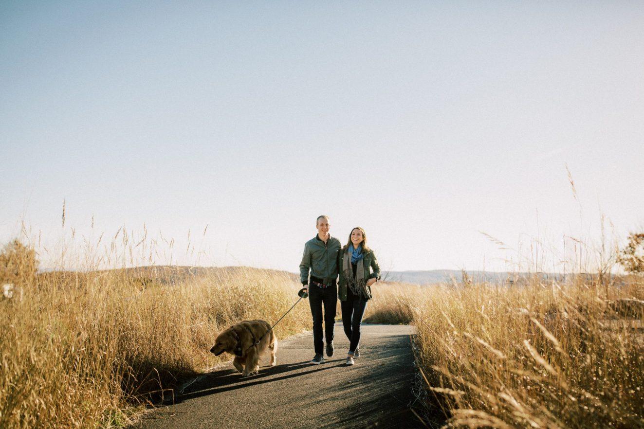 couple walking with a golden retriever on Bear Mountain NY